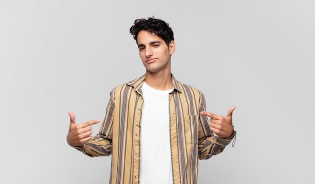 Giovane uomo bello che sembra orgoglioso, arrogante, felice, sorpreso e soddisfatto, indicando se stesso, sentendosi come un vincitore