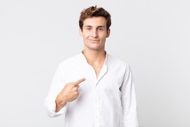 Giovane bell'uomo che sembra orgoglioso, fiducioso e felice, sorride e indica se stesso o fa il segno numero uno