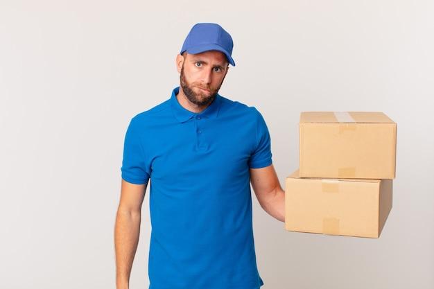 Giovane uomo bello che sembra perplesso e confuso. concetto di consegna del pacchetto
