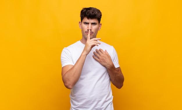 Giovane uomo bello che sembra serio e croce con il dito premuto sulle labbra che chiedono silenzio o silenzio, mantenendo un segreto