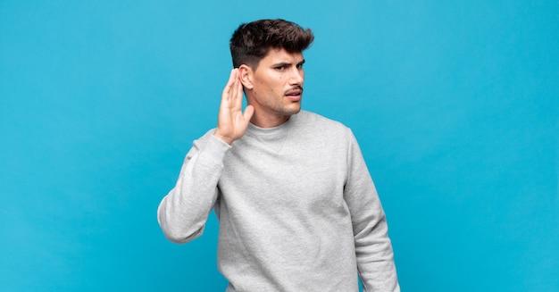 Giovane uomo bello che sembra serio e curioso, ascolta, cerca di ascoltare una conversazione segreta o pettegolezzi, origliare