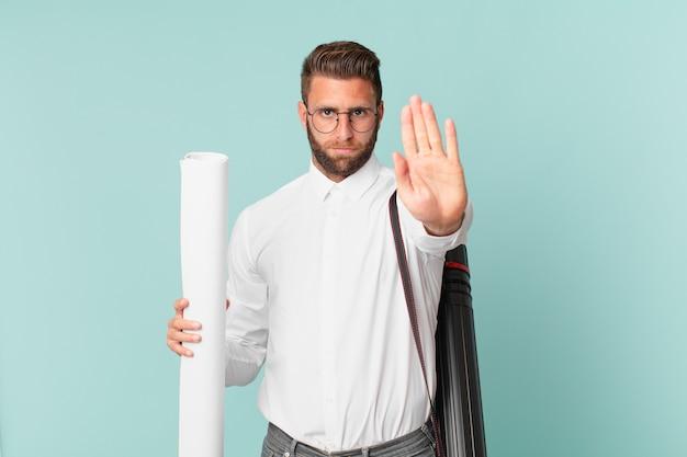 Giovane uomo bello che sembra serio mostrando palmo aperto che fa gesto di arresto. concetto di architetto