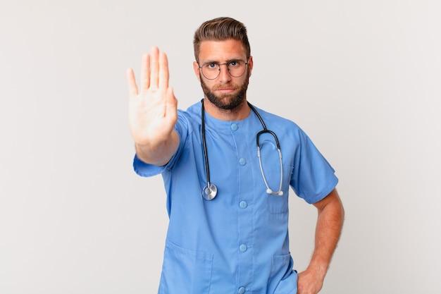 Giovane uomo bello che sembra serio mostrando palmo aperto che fa gesto di arresto. concetto di infermiera