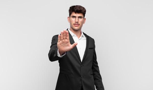 Giovane uomo bello che sembra serio, severo, dispiaciuto e arrabbiato mostrando il palmo aperto che fa gesto di arresto