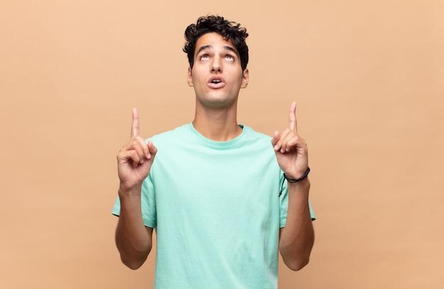 Giovane uomo bello che sembra scioccato, stupito e con la bocca aperta, rivolto verso l'alto con entrambe le mani per copiare lo spazio