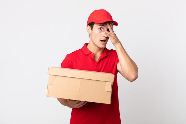 Giovane uomo bello che sembra scioccato, spaventato o terrorizzato, che copre il viso con il concetto di servizio di consegna a mano.