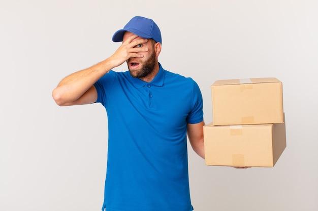 Giovane bell'uomo che sembra scioccato, spaventato o terrorizzato, coprendo il viso con la mano. concetto di consegna del pacchetto