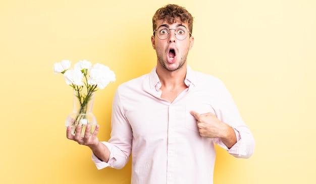 Giovane bell'uomo che sembra scioccato e sorpreso con la bocca spalancata, che indica se stesso. concetto di fiori