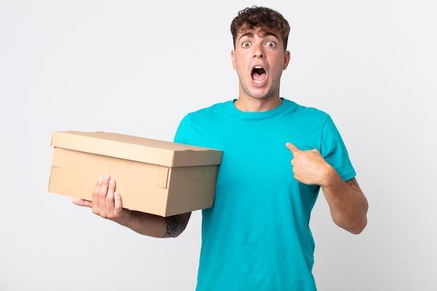 Giovane bell'uomo che sembra scioccato e sorpreso con la bocca spalancata, che indica se stesso e tiene in mano una scatola di cartone
