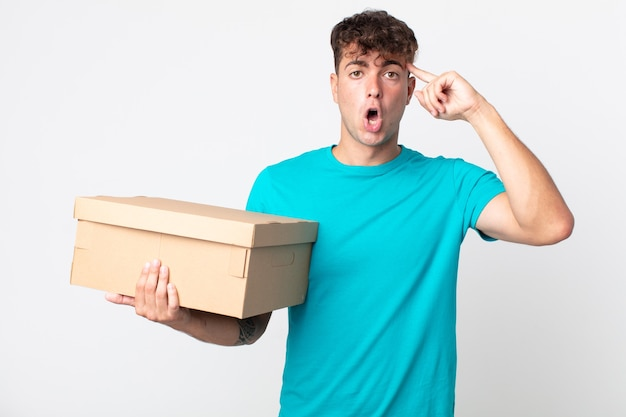 Giovane bell'uomo che sembra sorpreso, realizzando un nuovo pensiero, idea o concetto e tenendo in mano una scatola di cartone