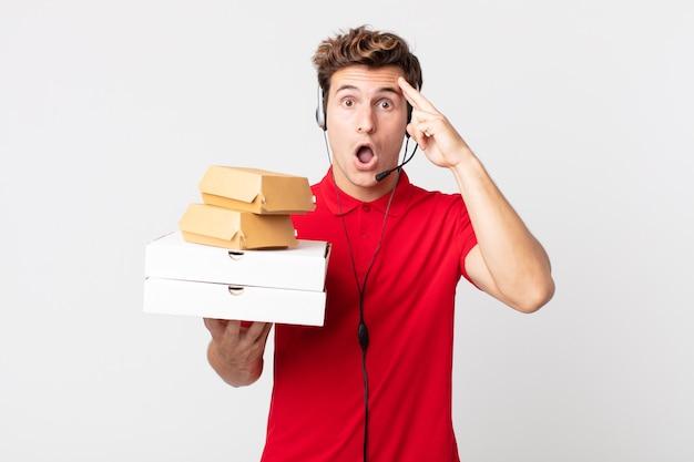 Giovane uomo bello che sembra sorpreso, realizzando un nuovo pensiero, idea o concetto. porta via il concetto di fast food