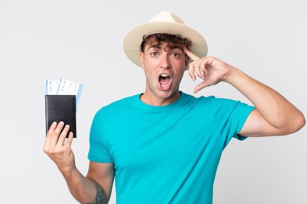 Giovane uomo bello che sembra sorpreso, realizzando un nuovo pensiero, idea o concetto. viaggiatore con in mano il passaporto