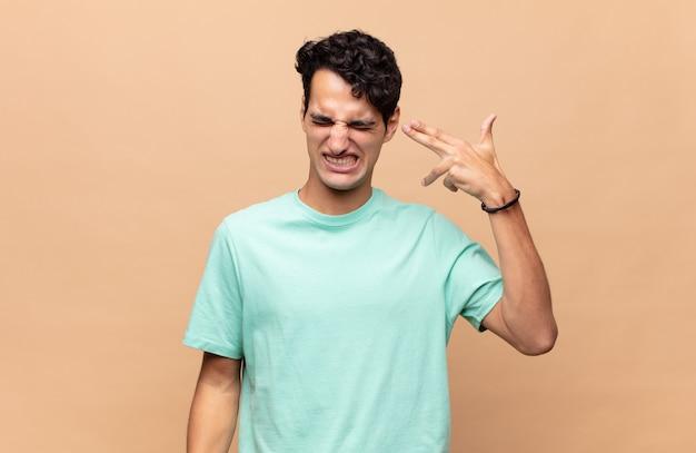 Giovane uomo bello che sembra infelice e stressato, gesto di suicidio che fa segno di pistola con la mano, indicando la testa