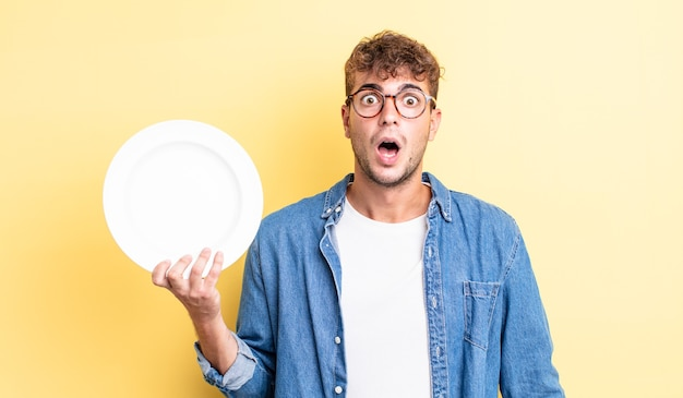 Giovane uomo bello che sembra molto scioccato o sorpreso. concetto di piatto vuoto
