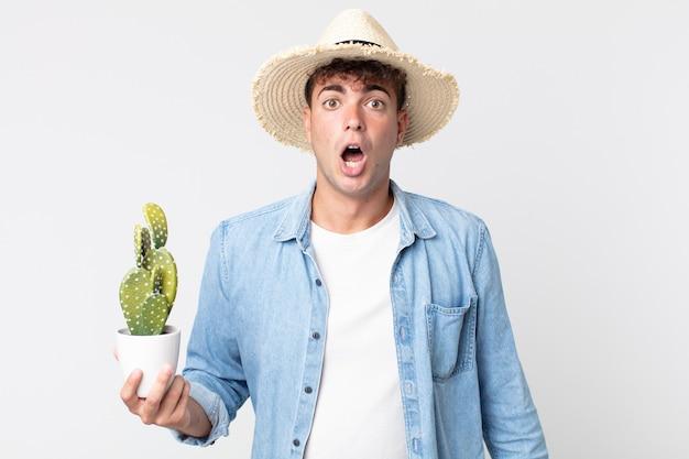 Giovane uomo bello che sembra molto scioccato o sorpreso. contadino con in mano un cactus decorativo