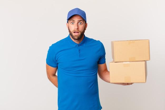 Giovane uomo bello che sembra molto scioccato o sorpreso. concetto di consegna del pacchetto