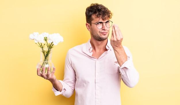 Giovane bell'uomo che fa un gesto di denaro o di denaro, dicendoti di pagare. concetto di fiori
