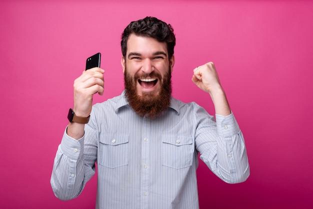 Giovane uomo bello che fa un gesto del vincitore con il telefono in sua mano.