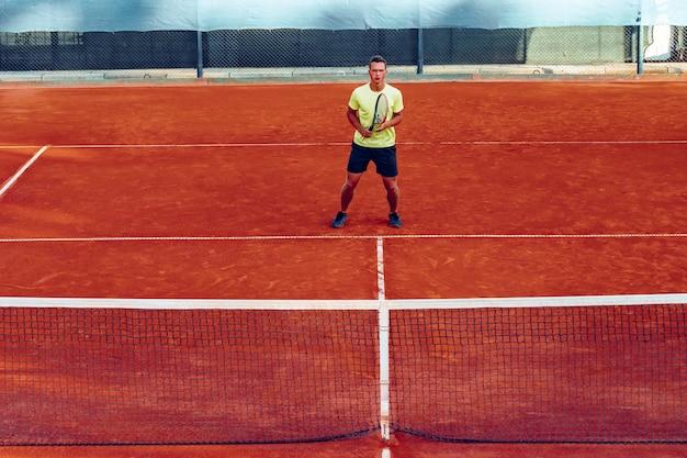 Giovane uomo bello giocare a tennis sul campo da tennis in terra battuta