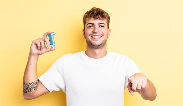 Giovane uomo bello che punta alla telecamera scegliendo te. concetto di asma