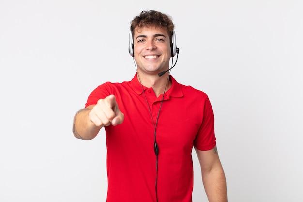 Giovane uomo bello che punta alla telecamera scegliendo te. concetto di telemarketing