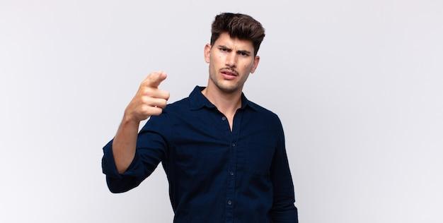 Giovane uomo bello che indica alla macchina fotografica con un'espressione aggressiva arrabbiata che assomiglia a un capo furioso e pazzo