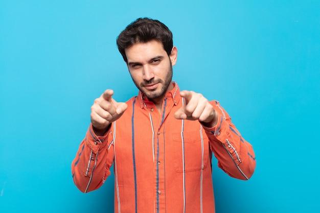 Giovane uomo bello che punta in avanti alla telecamera con entrambe le dita e l'espressione arrabbiata, dicendoti di fare il tuo dovere