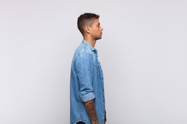 Giovane uomo bello in posa su grigio