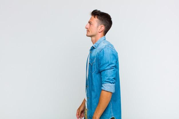 Giovane uomo bello sulla vista di profilo guardando avanti, pensando, immaginando o sognando ad occhi aperti