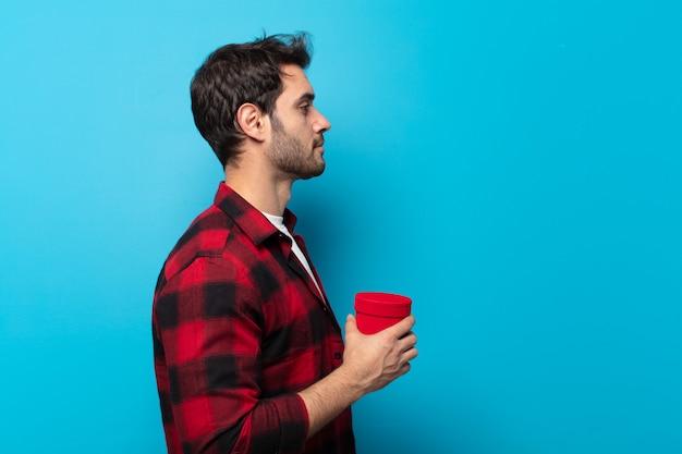Giovane uomo bello sulla vista di profilo che cerca di copiare lo spazio davanti, pensare, immaginare o sognare ad occhi aperti