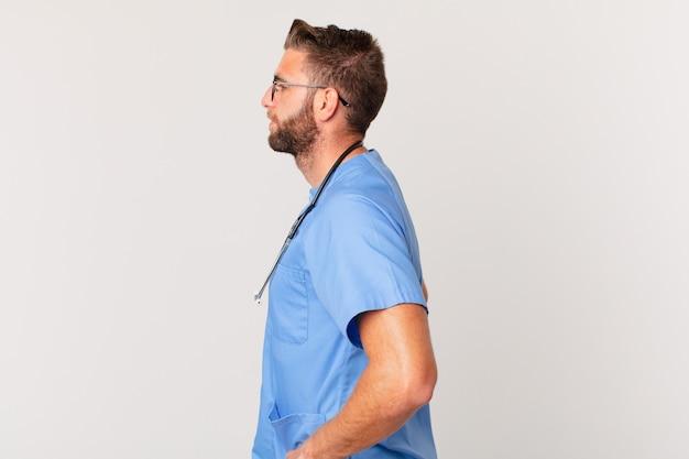 Giovane uomo bello sulla vista di profilo pensando, immaginando o sognando ad occhi aperti. concetto di infermiera