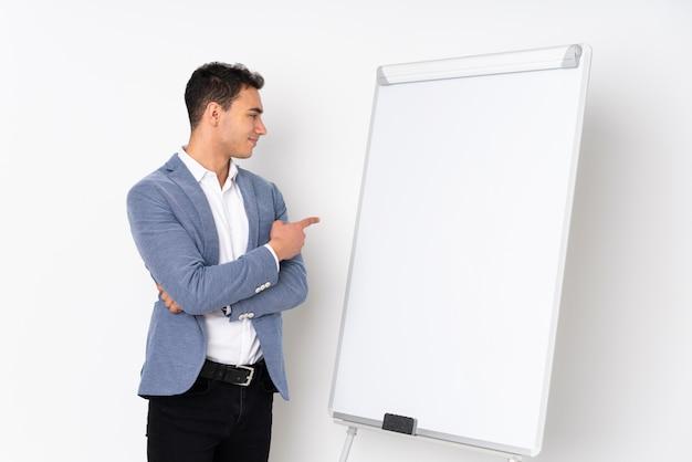 Giovane uomo bello sulla porpora che dà una presentazione sul bordo bianco e che lo indica