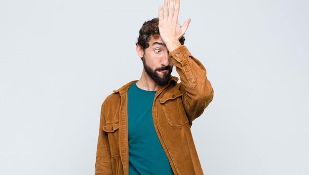 Giovane uomo bello che alza il palmo alla fronte pensando oops, dopo aver commesso uno stupido errore o aver ricordato, sentendosi stupido contro il muro piatto