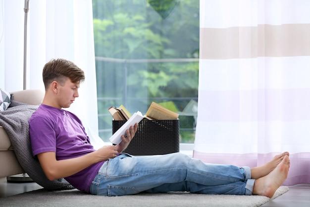 Giovane bell'uomo che legge un libro a casa