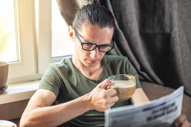 Un giovane uomo bello leggere interessanti articoli di notizie calde in un giornale e bere una tazza di cappuccino