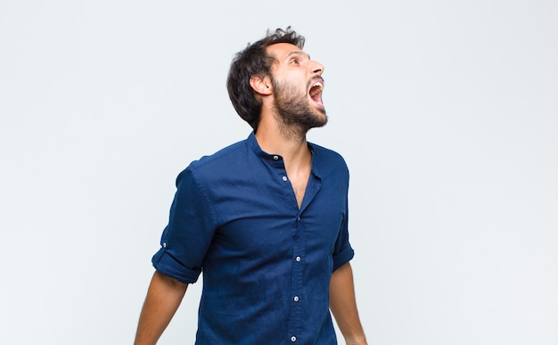 Giovane uomo bello che grida furiosamente, grida in modo aggressivo, sembra stressato e arrabbiato