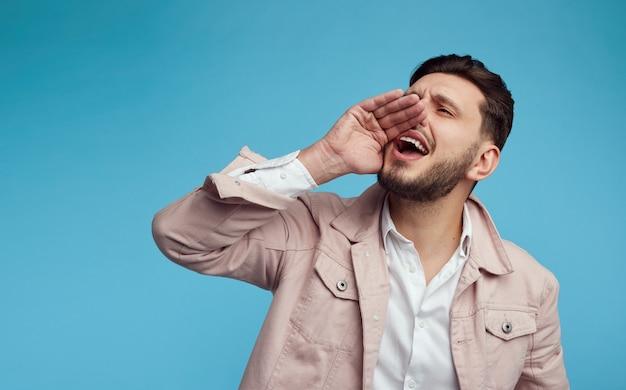 Giovane uomo bello che urla con la mano vicino alla bocca su sfondo blu studio