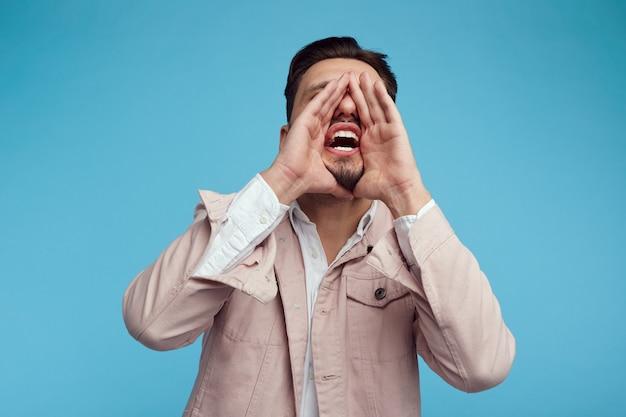 Giovane uomo bello che grida con la mano vicino alla bocca sulla parete blu dello studio