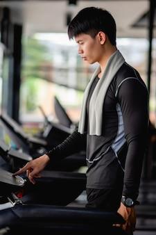 Programma di impostazione del giovane uomo bello in esecuzione per un sano allenamento in pista nella moderna palestra,
