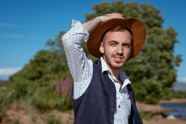 Il giovane bell'uomo con una camicia e un cappello sulla natura guarda di lato durante il giorno d'estate