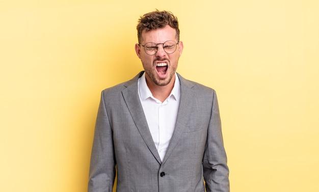 Giovane bell'uomo che grida in modo aggressivo, sembra molto arrabbiato. concetto di business