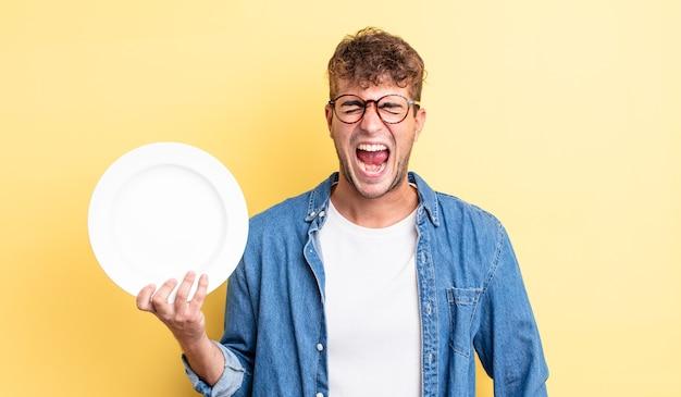 Giovane bell'uomo che grida in modo aggressivo, sembra molto arrabbiato. concetto di piatto vuoto