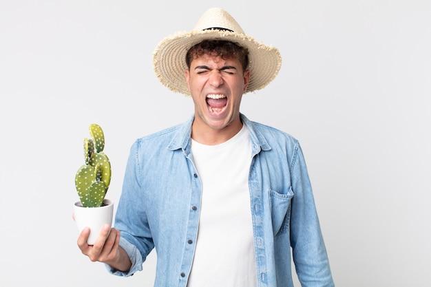 Giovane bell'uomo che grida in modo aggressivo, sembra molto arrabbiato. contadino con in mano un cactus decorativo
