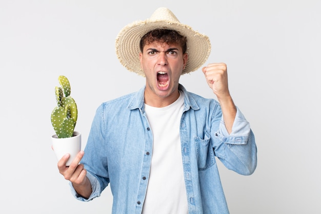 Giovane uomo bello che grida in modo aggressivo con un'espressione arrabbiata. contadino con in mano un cactus decorativo
