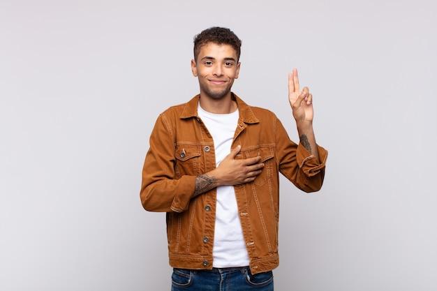 Giovane uomo bello che mostra gesto di pace
