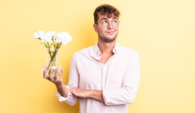 Giovane bell'uomo che scrolla le spalle, sentendosi confuso e incerto. concetto di fiori