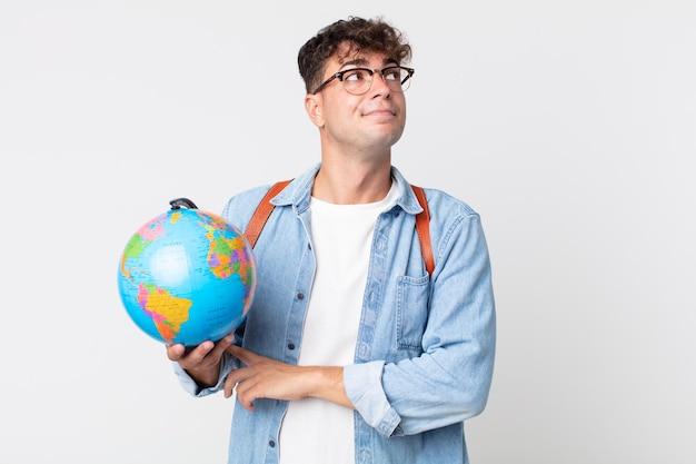 Giovane bell'uomo che alza le spalle, sentendosi confuso e incerto. studente con in mano una mappa del globo