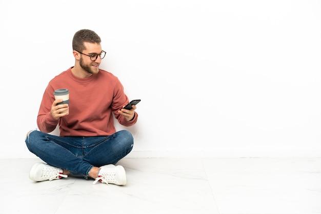 Giovane uomo bello che si siede sul pavimento che tiene il caffè da portare via e un cellulare