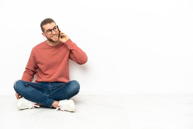 Giovane uomo bello seduto sul pavimento mantenendo una conversazione con il telefono cellulare con qualcuno