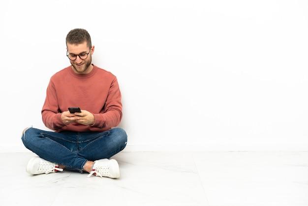 Giovane uomo bello seduto sul pavimento inviando un messaggio con il cellulare